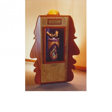 Joel's Ark ~ Vermillion wood faces, oak cabinet, walnut hands, fabric torah cover, cast resin flame. A triangular shaped cabinet for honoring scholars whose names are engraved on brass plaques. In honor of the memory of a best friend Joel Polsky.